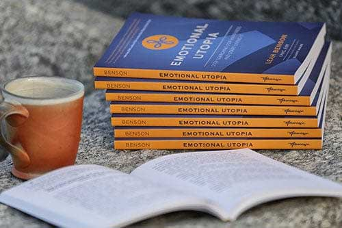 stack of emotional utopia books by a cup of coffee