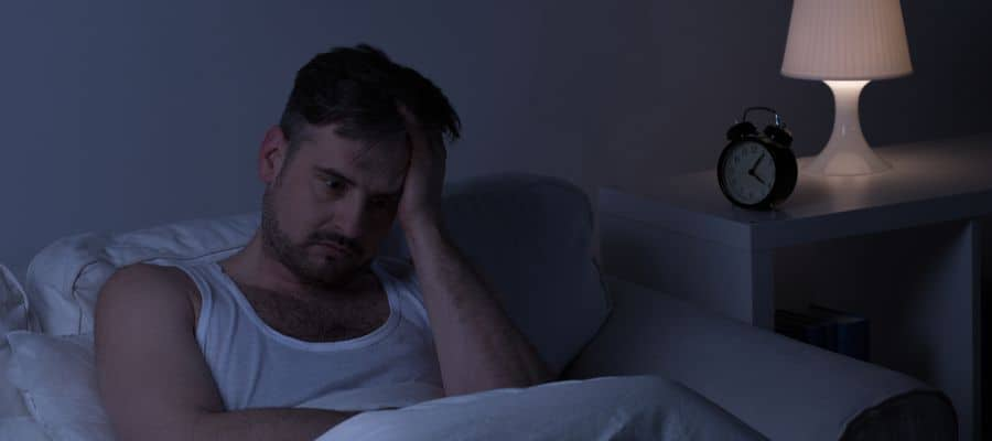 man stressed laying in bed