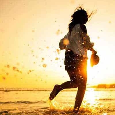 woman running on beach sunset